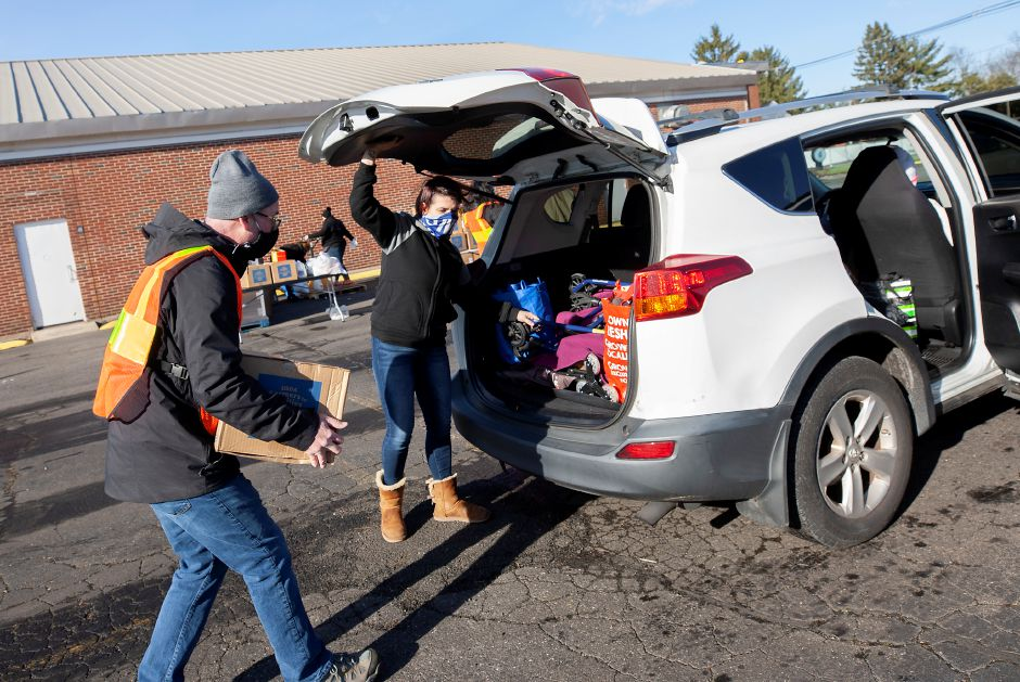 Kristen Fortin, of Wallingford, holds the hatch open for volunteer Toby Cofiell, of Glastonbury, who carries a box of food to her vehicle during a Farmers to Families Food Box distribution in partnership with the United Way of Meriden and Wallingford at Good News Christian Church in Wallingford, Tues., Dec. 15, 2020. Food boxes contained a combination of fresh produce, dairy and meat products. Dave Zajac, Record-Journal
