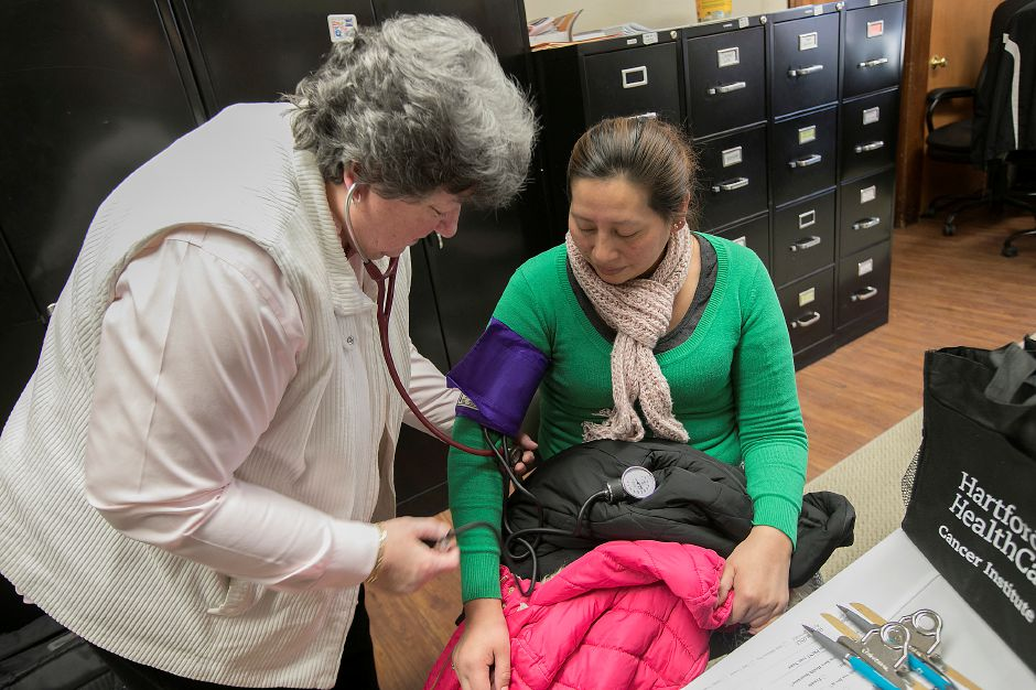 Sandra Dominguez, of Meriden, gets her blood pressure taken by MidState Community Nurse Educator, Donna Jones, during a free adult health screening at Head Start in Meriden on Thursday.                                                                                                        Photos by Dave Zajac, Record-Journal