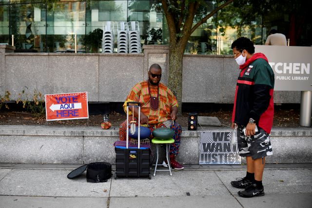 "CORRECTS CITY TO HARTFORD INSTEAD OF GLASTONBURY - Arrow Howard plays a steel tongue drum he says to ""heal the community"" outside a polling place at the Hartford Public Library, Tuesday, Aug. 11, 2020, in Hartford, Conn. (AP Photo/Jessica Hill)"