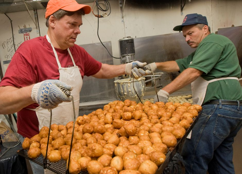 Russ Christensen, of Southington, left, carries a hot basket of freshly fried apple fritters next to Eric Kuhr, of Southington, in the Zion Lutheran Church tent on opening night of the 48th Annual Apple Harvest Festival in Southington, Friday, September 30, 2016. The festival runs September 30, October 1-2 & October 7-9. | Dave Zajac, Record-Journal