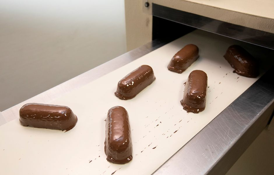 Chocolate-covered Twinkies cool down on a conveyor at Rosie