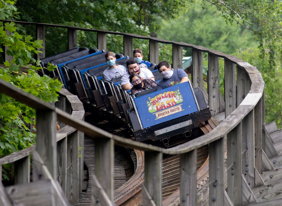 Riders wear their mask as they ride Boulder Dash at Lake Compounce on Tuesday. Visitors must wear a mask throughout the park and on rides and will be seated by ride attendants for proper distancing.