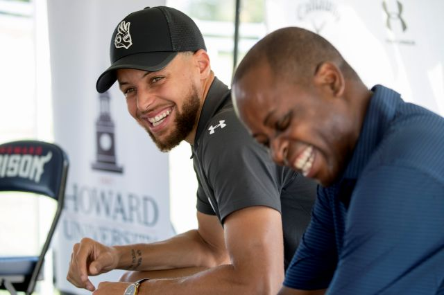 Golden State Warriors guard Stephen Curry, left, and Howard University President Wayne Frederick laugh before a news conference Monday at Langston Golf Course in Washington, where Curry announced that he would be sponsoring men's and women's golf teams at Howard University.Associated Press