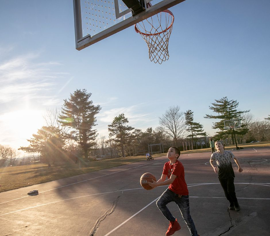 The sun beams down on Brian Vives, 12, of Meriden, who takes a shot in front of friend, Nathan Murphy, 13, of Berlin, during an unusually warm winter afternoon at Ceppa Field in Meriden, Tues. Feb. 5, 2019. Dave Zajac, Record-Journal