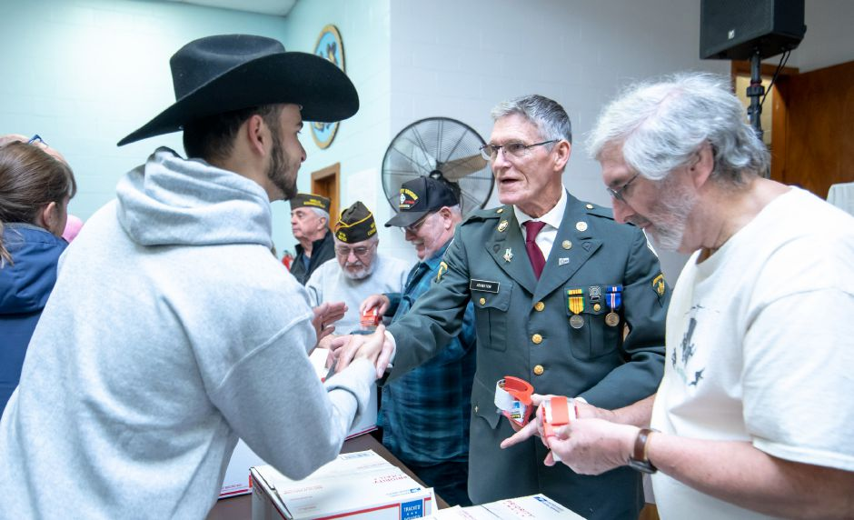 A veteran shakes hands with a volunteer for the Hero Boxes care package packing day, held at the New Britain Veterans of Foreign Wars post on Nov. 9, 2019. The Berlin-based non-profit sends hundreds of care packages to soldiers serving in war zones each year. | Devin Leith-Yessian/Berlin Citizen