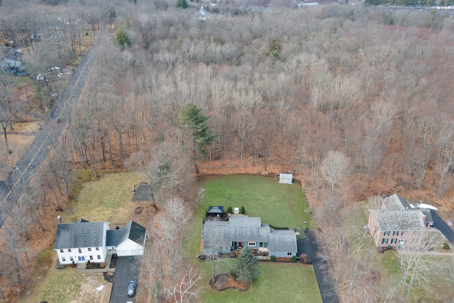 View looking west shows a wooded area proposed for a housing development behind homes on Doral Lane off Laning Street in Southington. The long delayed age-restricted housing project is slated for discussion at Tuesday's Planning and Zoning Commission meeting. | File photo