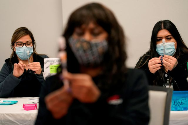 FILE - In this Jan. 22, 2021, file photo, certified medical assistants Martha Sida, from left, Tina Killebrew and Cynthia Bernal prepare doses of the Pfizer-BioNTech COVID-19 vaccine at a vaccination center at the University of Nevada, Las Vegas, in Las Vegas. COVID-19 vaccine makers tell Congress to expect a big jump in the delivery of doses over the coming month. The companies insisted Tuesday, Feb. 23, at a hearing that they will be able to provide enough vaccine for most Americans...