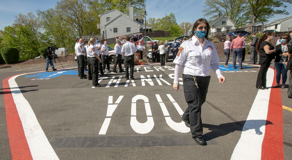 "Erin Morrow, operations supervisor, walks over a heart painted on the ground that reads ""HUNTERS THANKS YOU""  after a ceremony honoring EMS staff during National EMS Week at Hunter's Ambulance in Meriden on Tuesday. Photos by Dave Zajac, Record-Journal"