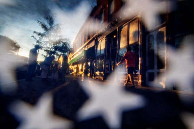 The sun sets on Main Street, as seen through a U.S. flag, Saturday, Aug. 31, 2019, in Trumansburg, N.Y., where earlier in the day a memorial procession passed through for Sgt. James Johnston, who was killed in Afghanistan in June. Two months after his death, his adopted hometown had come together over a holiday weekend to pay tribute, and to say goodbye. (AP Photo/David Goldman)