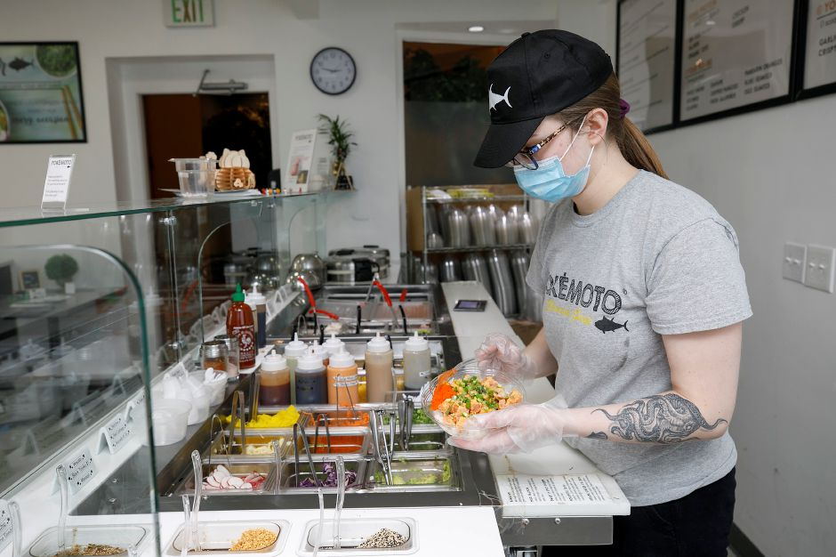 Server Sofia Drewniany prepares a Hawaiian Bowl for  takeout  at Pokémoto Hawaiian Poké in Middletown Friday. Pokémoto Hawaiian Poké is opening another location next to Chipotle in Wallingford. Dave Zajac, Record-Journal