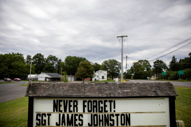 A sign remembering Sgt. James Johnston, who was killed in Afghanistan in June, stands outside the American Legion hall in Trumansburg, N.Y., Sunday, Sept. 1, 2019. As the nation