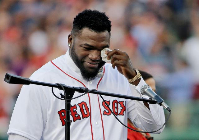 "FILE - In this June 23, 2017, file photo, Boston Red Sox baseball great David Ortiz wipes a tear at Fenway Park in Boston as the team retires his number ""34"" worn when he led the franchise to three World Series titles. Ortiz was back in Boston for medical care after authorities said the former Red Sox slugger affectionately known as Big Papi was ambushed by a gunman at a bar in his native Dominican Republic. A plane carrying the 43-year-old retired athlete landed Monday night, June 10, 2019, after a flight from the Dominican Republic, the team said.  (AP Photo/Elise Amendola, File)"