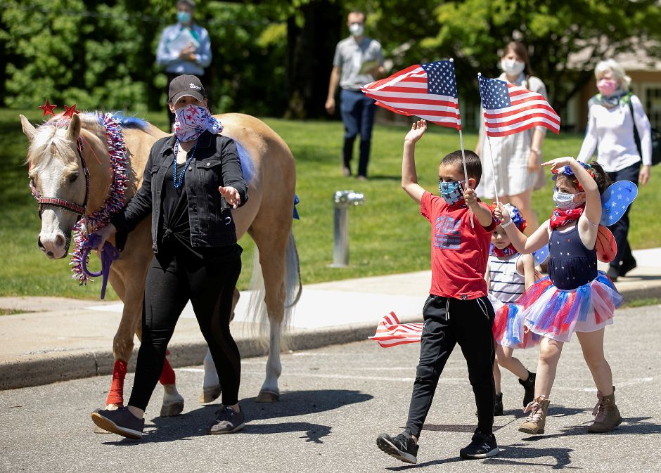 "Kelsey Nemarich, of Avon, guides horse ""Legally Blonde"" next to children, Berkeley, 7, Nola, 3, and Poppy, 6 who wave during a pony parade for patients and staff at Gaylord Specialty Healthcare in Wallingford in honor of Memorial Day, Thurs., May 21, 2020. The parade featured ponies from Pembroke Hill Equestrian and their owners and children that train at the Avon based stable. Dave Zajac, Record-Journal"