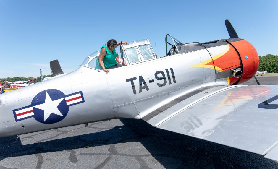 Jannett Johnson climbs into a North American AT-6A Texan during the Wings and Wheels car and air show at Robertson Airport in Plainville on June 8, 2019. | Devin Leith-Yessian/Plainville Citizen