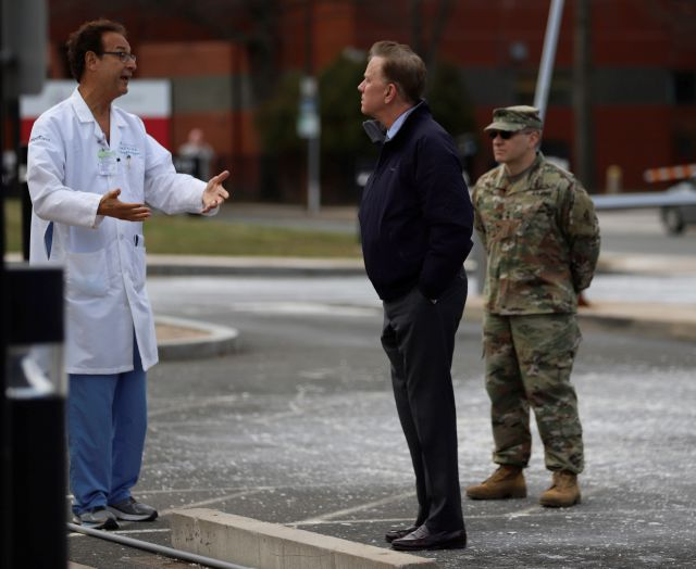 Saint Francis Hospital and Medical Center President John Rodis, M.D., left, speaks with Connecticut Gov. Ned Lamont outside Saint Francis Hospital, Tuesday, March 24, 2020. Rodis said they are trying to preserve the supplies they have at the hospital and has also seen a reduction in emergency department visits. (AP Photo/Chris Ehrmann)