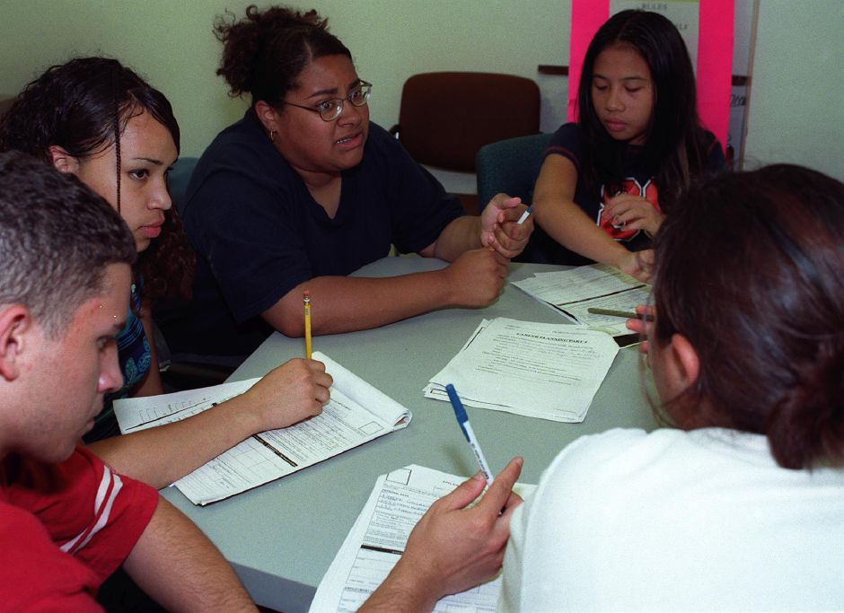 From left to right: Heberto Collazo, 16, Grisell Matos, 15, Sheena Soto, 15, Jade Supapo, 14, and Crystal Valadez, front, 16, all part of the Summer Youth Employment program, discuss careers and schools while filling out career planning worksheets at the Youth Services office on Wednesday afternoon Aug. 9, 2000.