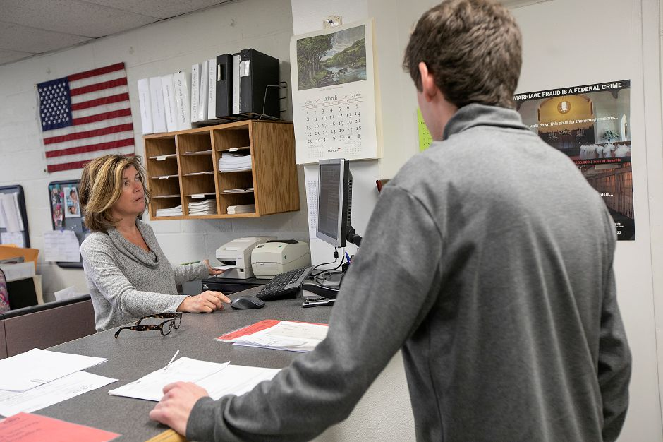 Town Clerk Barbara Thompson, left,  assists RJ Strollo, of Cheshire, in the Town Clerk office at Wallingford Town Hall on Monday.