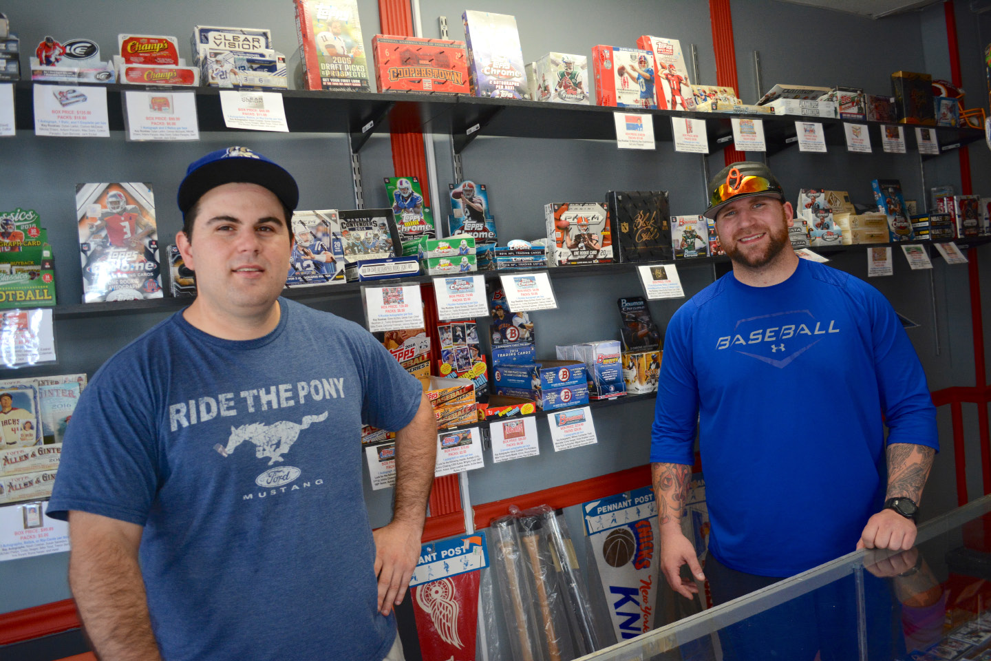 Front Row co-owners David Giglio and William Senna III at their shop on Quinnipiac Street in Wallingford. Below, a Roberto Clemente giant bobblehead on display at the shop.| Photos by Bryan Lipiner, Record-Journal