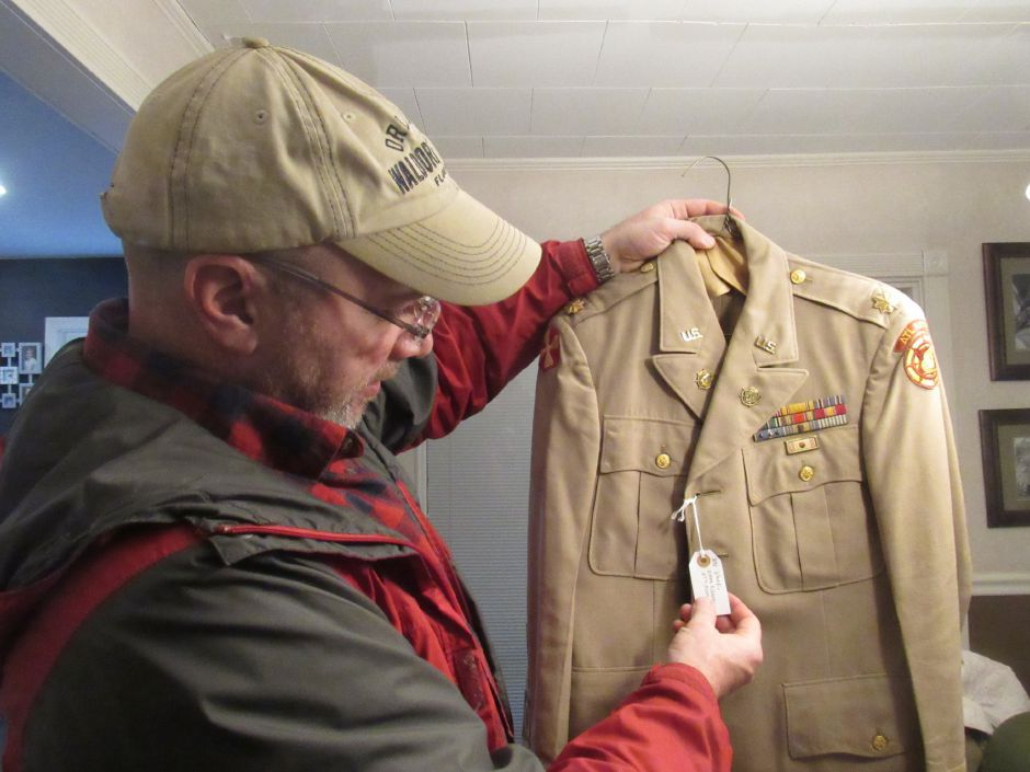 Wallingford resident Tom O'Rourke holds a vintage military uniform. O'Rourke hopes to open a military experience museum. | File photo