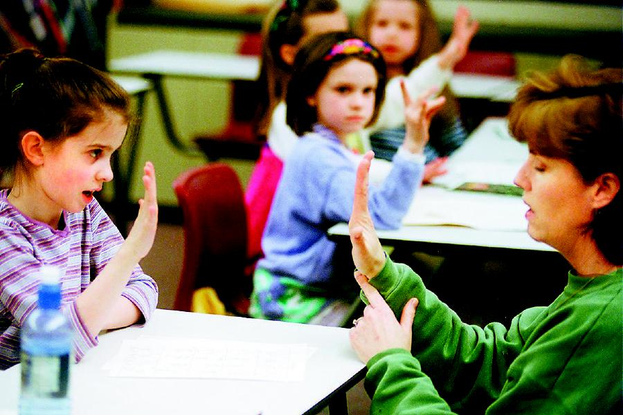 Sign language teacher Sandi Ciarciello, right, shows 2nd grader Taylor Altieri, left, how to sign during a class at Dodd Middle School Mon. night, March 27, 2000. In the back watching is Emily Phelan a 1st grader. The class was open to students from kindergarten through 3rd grade.