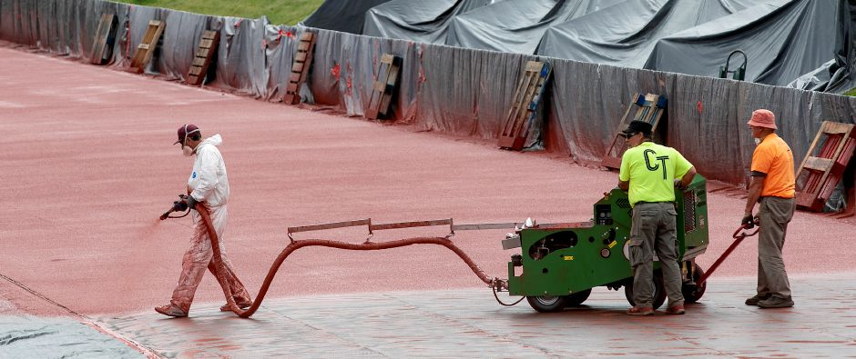 Work crews spray on the synthetic surface while constructing the new track at Platt High School in Meriden, Tues., Jun. 2, 2020. Dave Zajac, Record-Journal