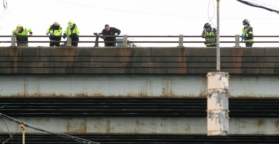 Emergency service crews and other personnel look down to Lewis Avenue in Meriden after an overturned dump truck on Interstate 691 eastbound caused debris to fall along the road March 1, 2021. Dave Zajac, Record-Journal