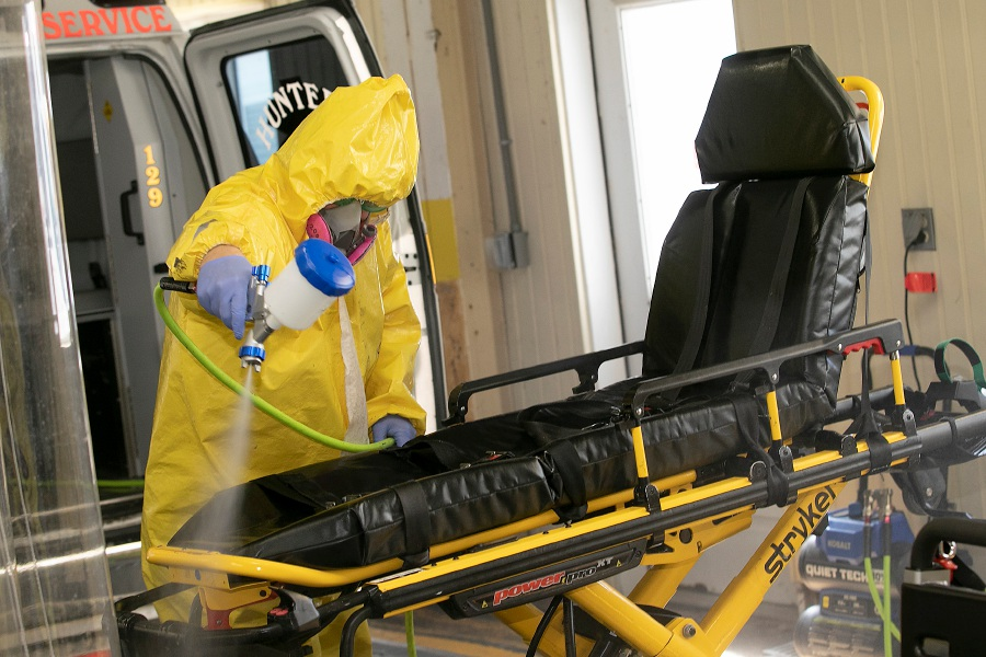 Decontamination team member Scott McMullen sprays down a stretcher with hydrogen peroxide Thursday at Hunter's Ambulance in Meriden. Vehicles and equipment are decontaminated after transporting possible COVID-19 patients. Dave Zajac, Record-Journal