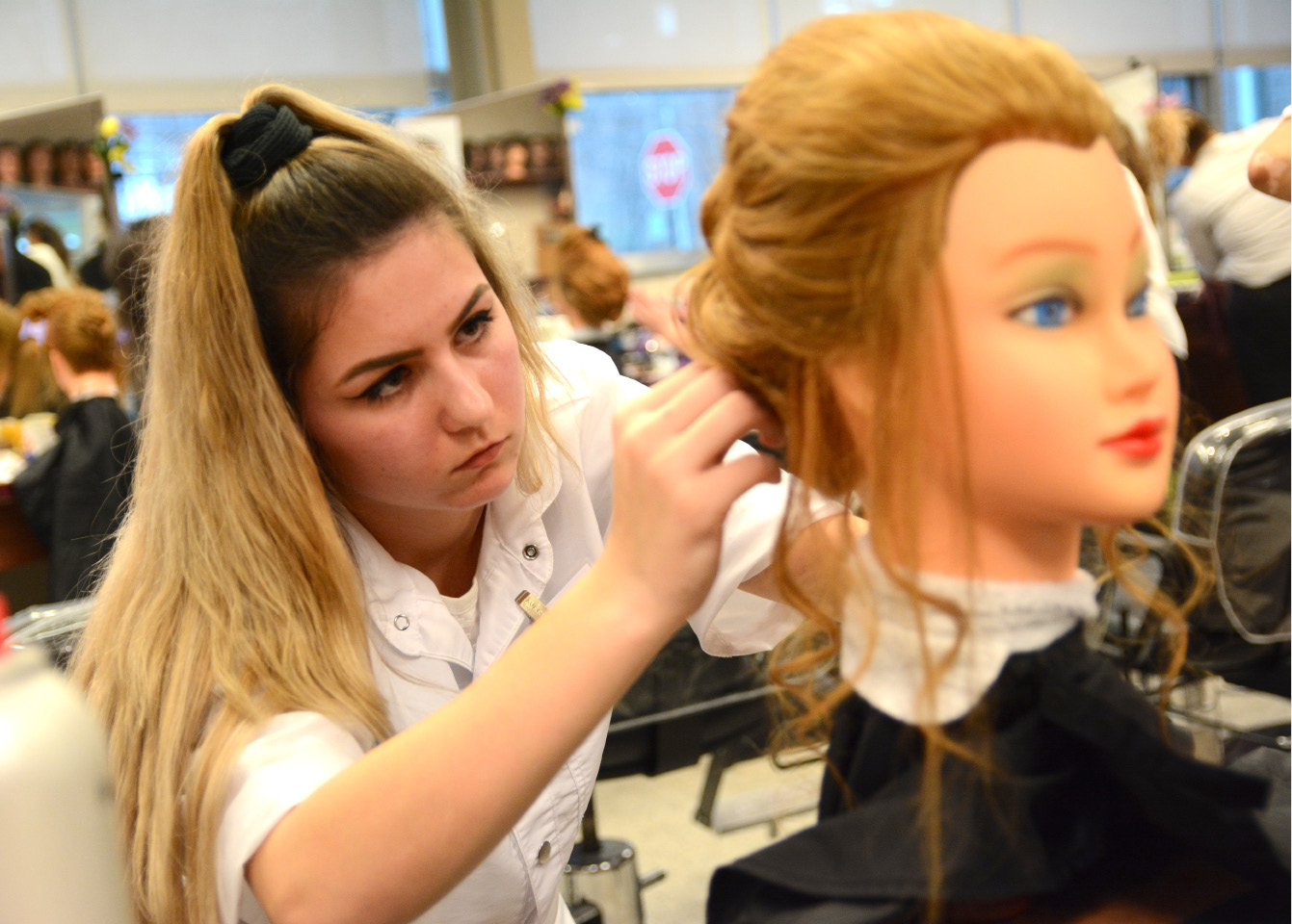 Sarena Tetreault, of Ellis Technical High School, creates an updo hairstyle during a Skills USA competition at Wilcox Technical High School on Friday, March 31, 2017. | Bryan Lipiner, Record-Journal