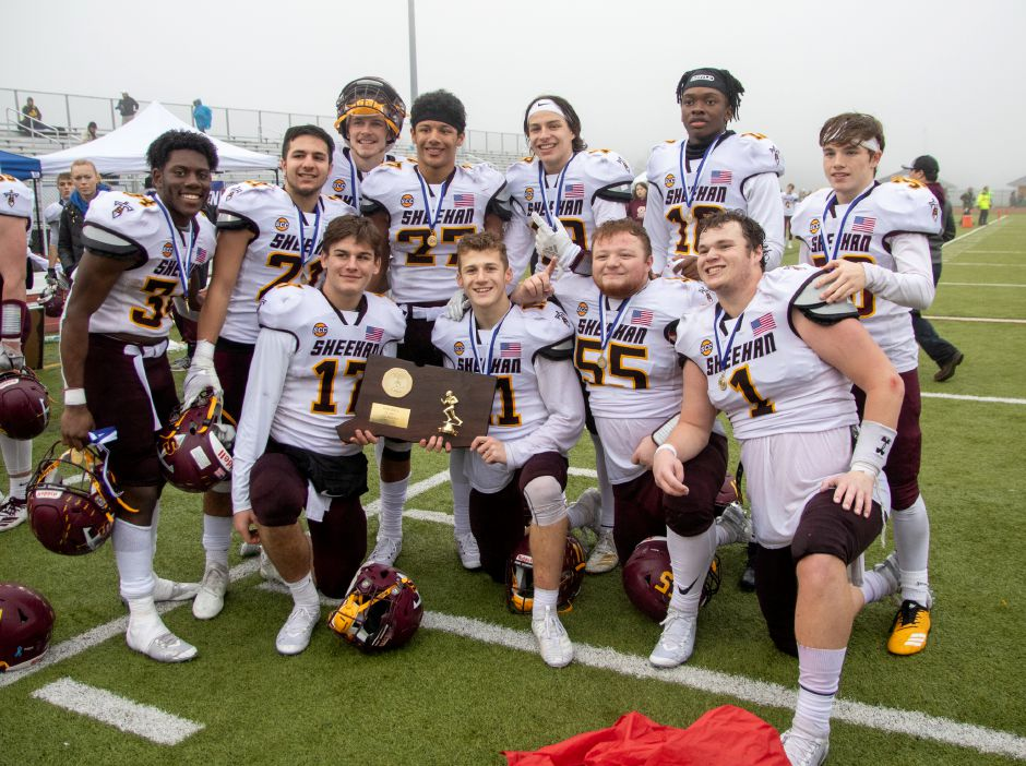 Sheehan seniors get their picture with the plaque after winning the CIAC Class S Championship Football game against Brookfield. Aaron Flaum, Record-Journal