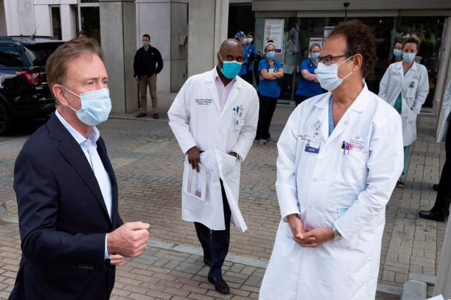 Gov. Ned Lamont  left, talks with medical staff outside Saint Francis Hospital in Hartford in this July file photo. (AP Photo/Mark Lennihan)