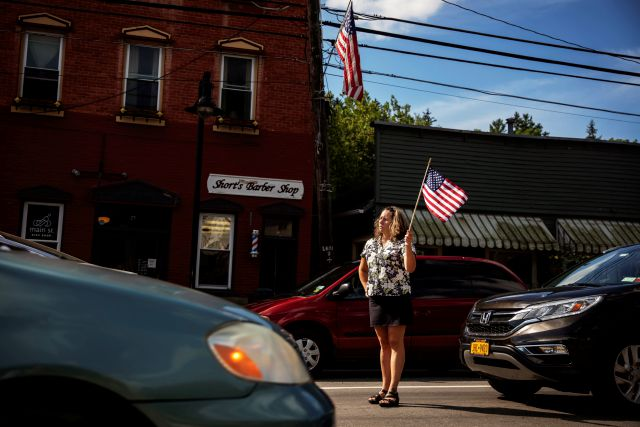 Sarah Short stands outside her barber shop to watch a memorial procession pass through Trumansburg, N.Y., Saturday, Aug. 31, 2019, for Sgt. James Johnston, who was killed in Afghanistan in June. On this late summer Saturday, a procession of fire engines, motorcycles and squad cars were greeted by clusters of flag-waving folks. With its celebration of Johnston, the war came home to this hamlet in upstate New York. (AP Photo/David Goldman)