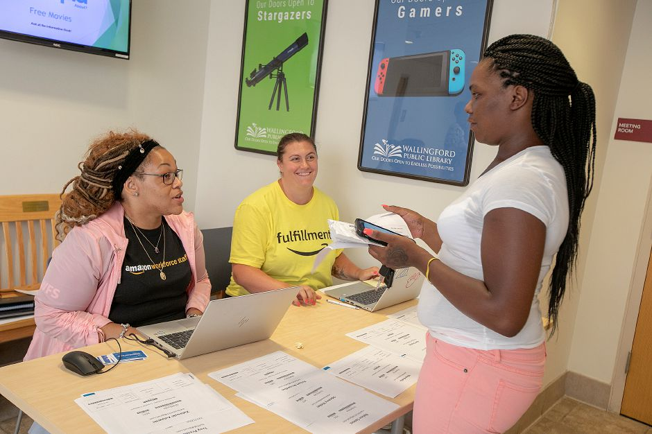 Shellick Douglas, of New Haven, checks in with Amazon representatives who declined to be identified during an Amazon hiring event at the Wallingford Public Library, Wednesday.