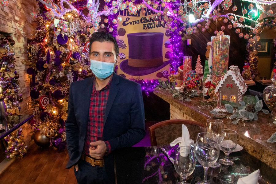 Tony Papahristou, manager of Cava Restaurant, stands in the Willy Wonka themed room on Wednesday.This is the restaurant's 13th year decorating for the holidays.