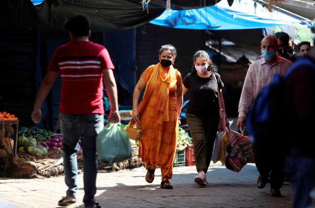 Indians wearing a face masks as a precaution against the coronavirus walk at a vegetables market in Jammu, India, Wednesday, Sept.23, 2020. The nation of 1.3 billion people is expected to become the pandemic