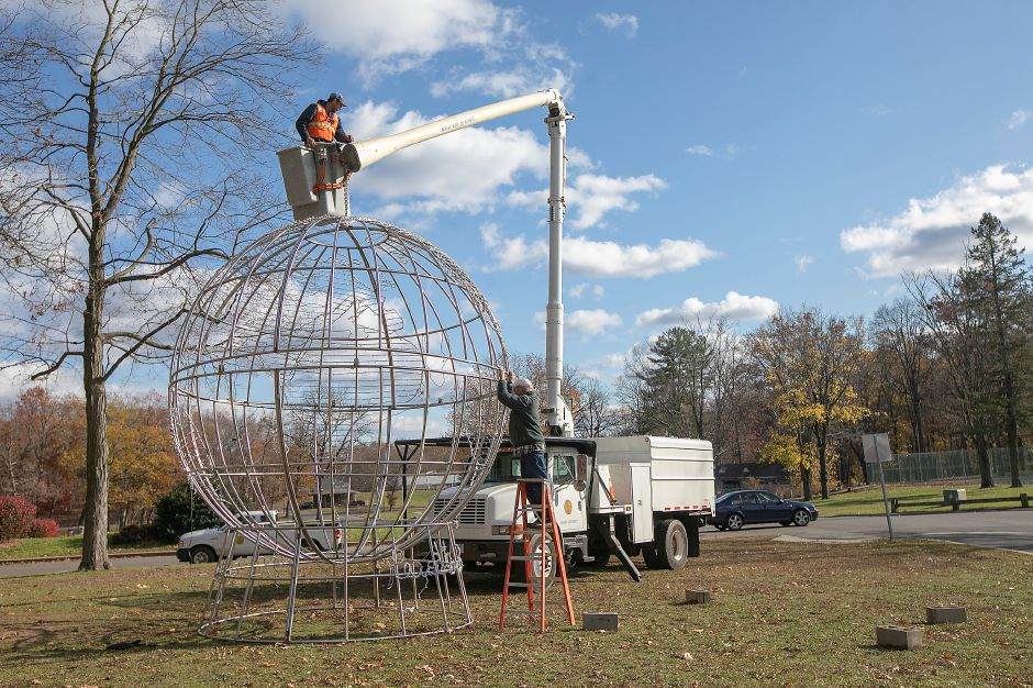 Park workers Jeremy Gaj, top, and Rob Zebora, right, assemble the Peace On Earth globe display while setting up for this year