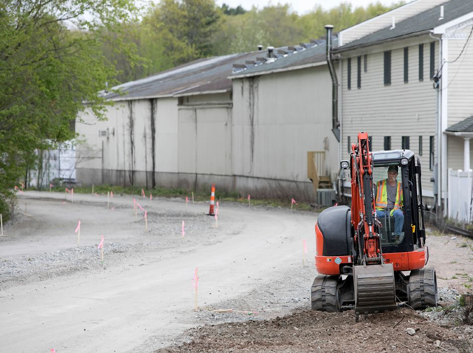 Mini-excavator operator, John Graham, cleans up the landscape along a new section of the Farmington Canal Heritage Trail between Cornwall Avenue and West Main Street in Cheshire, Thursday, May 10, 2018. Dave Zajac, Record-Journal