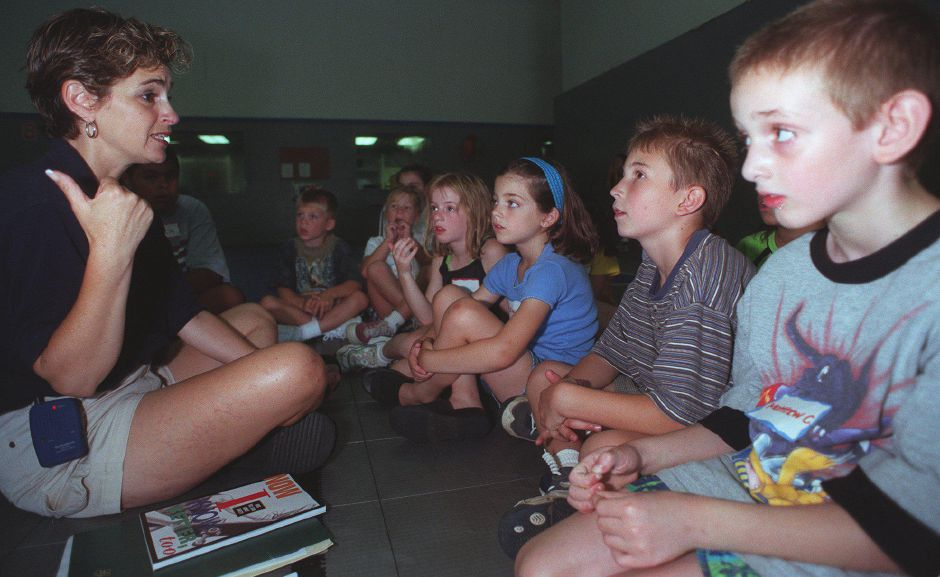 "Kim Garbatini, the director of summer camp ""Tiowa"" at Healthworks leads an interactive discusussion on the topic of strangers and kidnapping July 10, 2000. (From Right to Left) Matthew Caplan of Wallingford, Colin Polak of Meriden, Olivia Garbatini of Wallingford, and Kaitlin Gurgi of Wallingford think about what they would do in the different situations raised by Kim reguarding strangers."