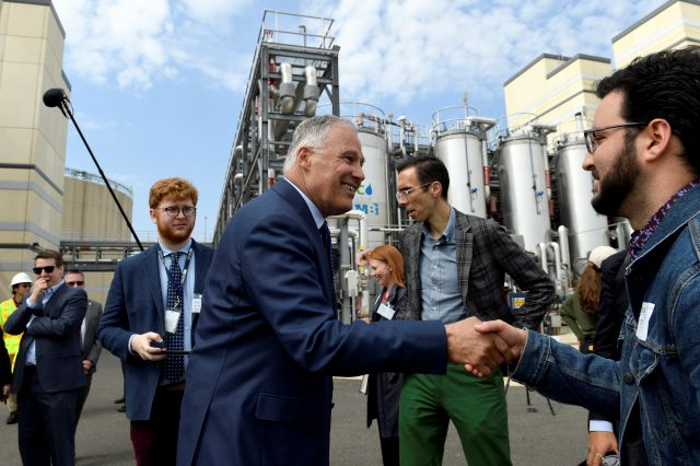 Democratic Presidential candidate Washington Gov. Jay Inslee, center, greets people as he tours the Blue Plains Advanced Wastewater Treatment Plant in Washington, Thursday, May 16, 2019, during an event where he unveiled part of his plan to defeat climate change. (AP Photo/Susan Walsh)