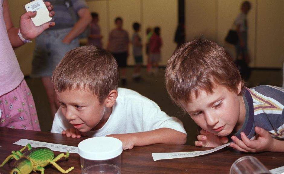 "Devin Flanagan, left, and Nicholas Fisher, both 7 and of Meriden, take a look at some of the bugs on display at the ""Incredible Insects"" presentation at the Meriden Public Library Monday evening Aug. 8, 2000."