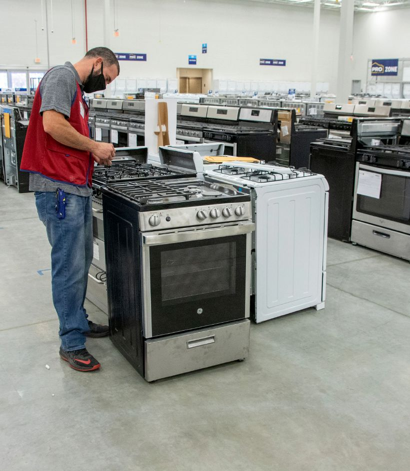 Lowe's Outlet appliance supervisor Victor Montanez places a gas stove onto the showroom floor.