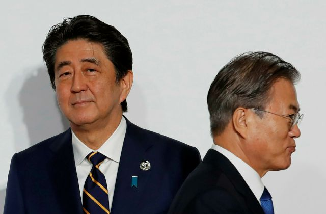 FILE - In this June 28, 2019, file photo, South Korean President Moon Jae-in, right, walks by Japanese Prime Minister Shinzo Abe upon his arrival for a welcome and family photo session at the G-20 leaders summit in Osaka, western Japan. South Korea said Thursday, Aug. 22, it is canceling an intelligence-sharing pact with Japan amid a bitter trade dispute, a surprise announcement that is likely to set back U.S. efforts to bolster mutual security cooperation with two of its most important...