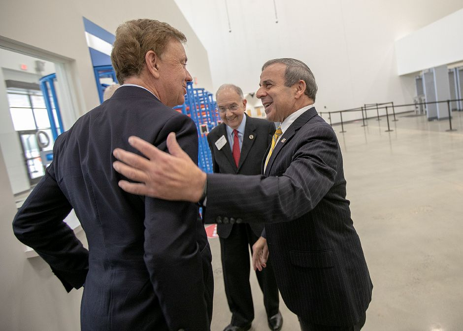 North Haven First Selectman Michael J. Freda, right, greets Governor Ned Lamont, left, next to Senator Martin M. Looney, center, before a tour of Amazon