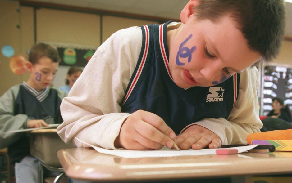 RJ file photo - Brian Sullivan, a fourth grader at Nathan Hale School in Meriden, works on a science project in class. Sullivan wore his team jersey and painted his face. Behind him Kyle Buonocore as the number 21 painted on his face in honor of UConn