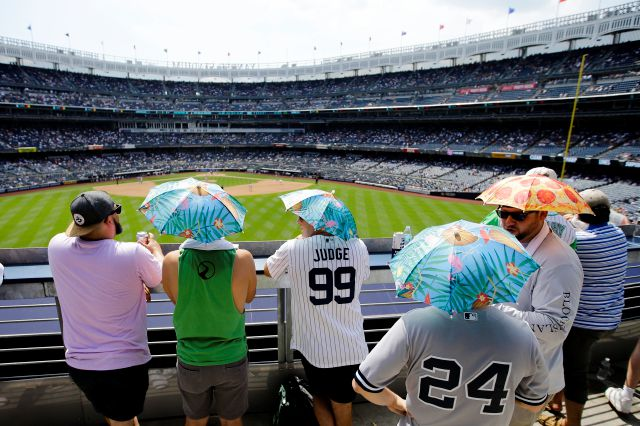 Fans use umbrella hats to protect themselves from the sun during the sixth inning of Saturday's game between the Yankees and Rockies in New York.