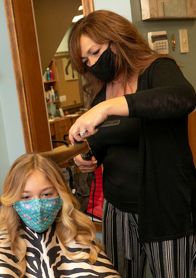 Catherine Stowik, owner of Catherine & Company Salon & Day Spa, curls the hair of her 11-year-old daughter Mia on Friday prior to a ribbon-cutting ceremony for the business at 710 E. Main St.  in Meriden. Catherine & Company Salon & Day Spa is celebrating 25 years. Dave Zajac, Record-Journal