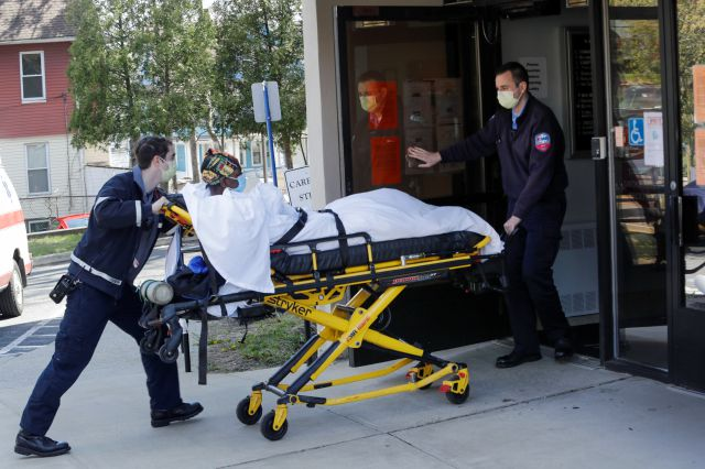 FILE - In this April 22, 2020, file photo medical workers bring a patient to the Northbridge Health Care Center in Bridgeport, Conn. A report from Senate Democrats finds that the Trump administration was slow to comprehend the scale of COVID-19
