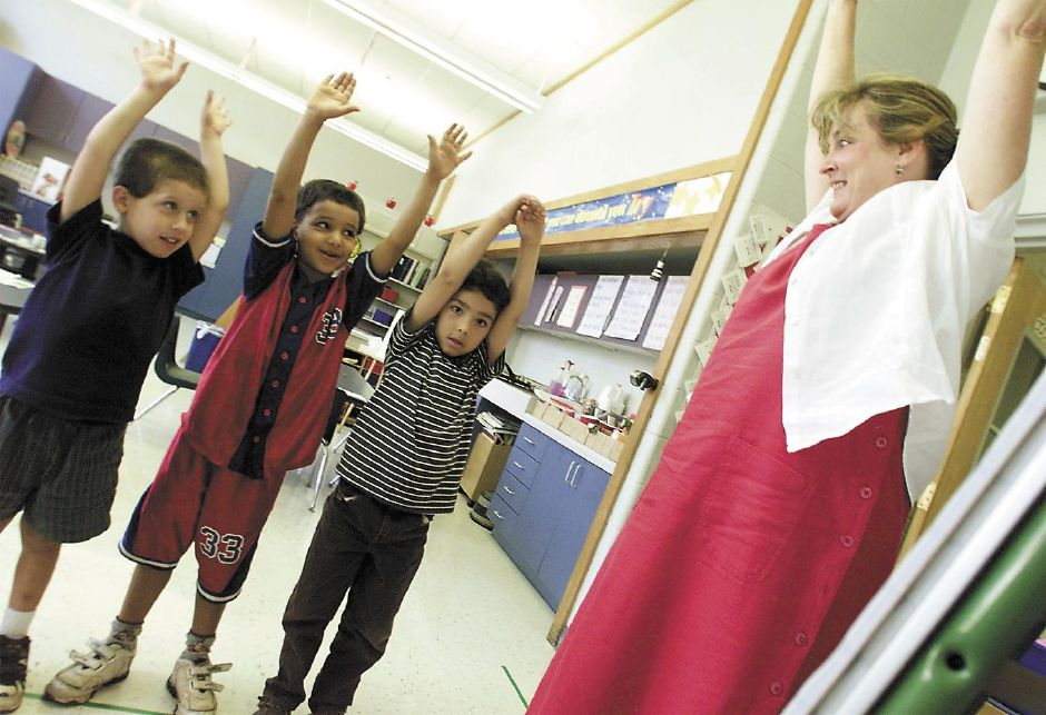 First grade teacher Marjorie Tucci (far right) helps students Jeremy Balogh, 5 (left), Abdellah Benamor, 5 and Irvin Gutierrez, 5 (right) form shapes of letter with their bodies to spell their names Aug. 10, 2000. The students are participating in a summer reading program at John Barry School.