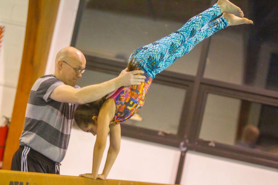Coach Jon Enger assists Angelica Delacruz on the balance beam in The Team Gymnastics Class offered by Girls Inc. | Ron Paris, Special to The Record-Journal