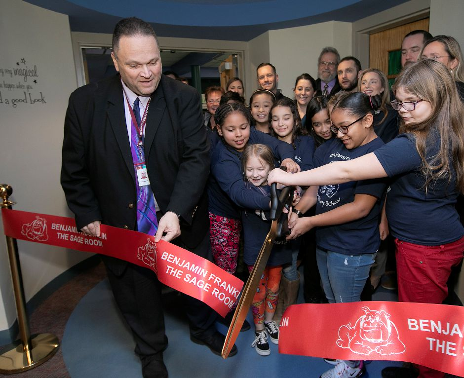 Meriden Board of Education President Rob Kosienski assists Art Club students with the ribbon-cutting for The Sage Room, a new mindfulness space at Benjamin Franklin Elementary School in Meriden, Fri., Feb. 21, 2020. The room encourages emotional regulation through the act of play, promotes a relaxing sensory experience and decreases stress and anxiety. Dave Zajac, Record-Journal