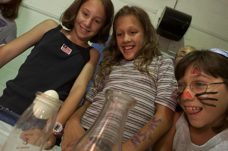 Lauren Smilovich, 11, left, Jordan Rivera, 10, middle, and Rebecca Carron, 10, right, all from Meriden, watch as an oxegen deprived match goes out, thus, sucking the egg through the bottle top. The three girls and others at Girls Inc. on Lincoln Street in Meriden, were showing off their science projects to parents and students at their Summer Science Fair Friday afternoon July 28, 2000.